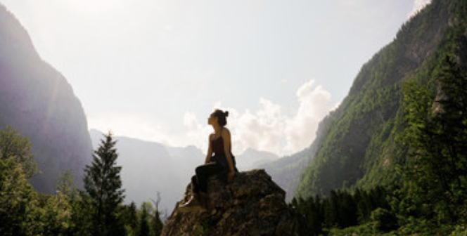 woman sitting on stone in nature